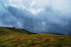 Stormy clouds on the sky over a mountain ridge covered with grass