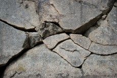 A basalt cracked stone wall with deep, black crevices