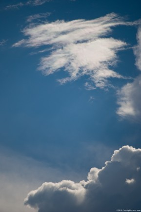 A clear sky between two layers of clouds: cumulus and cirrus