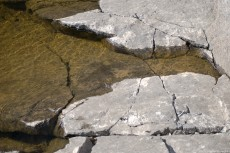 The combination of granite and water, as a lake and its edge