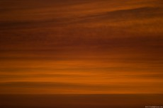 Sunset with red layers of clouds, in a dusty and smoky athmosphere