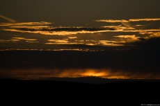 A sundown behind layers of clouds, in rusty shades